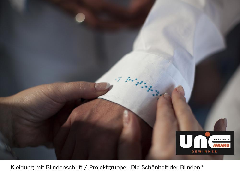 Bild von einer Hand, die das Kleidungsstück für Blinde berührt